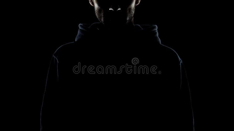 Uppsökt man som är osynlig i nattmörker, hemlig gangster, laglös avsikt royaltyfria foton