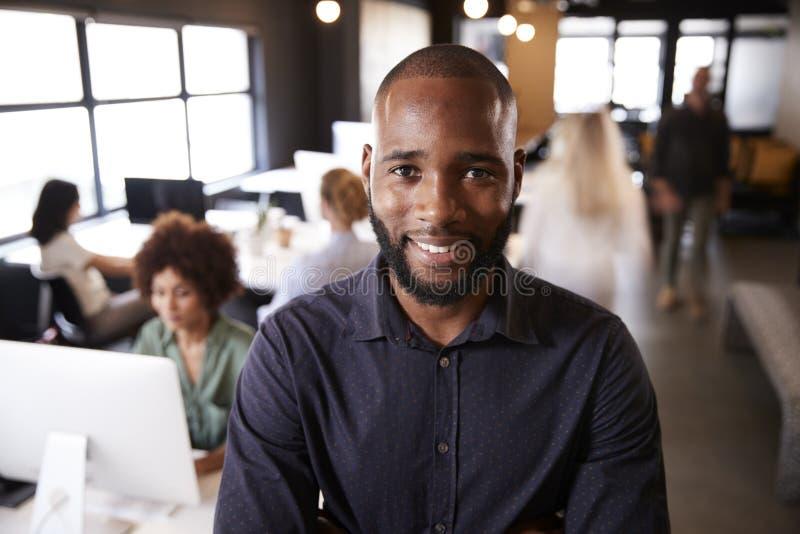 Uppsökt svart manligt idérikt anseende i ett upptaget tillfälligt kontor som ler till kameran royaltyfria bilder