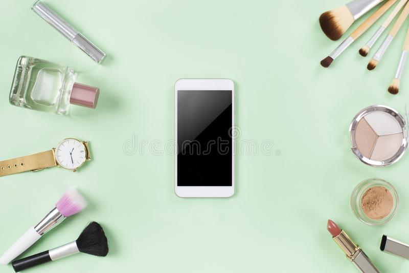 Upps?ttning av sminkborstar och sk?nhetsmedel med den smarta telefonen royaltyfri bild
