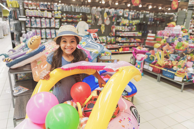 Uppsluppen le liten dam bland leksaker i supermarket royaltyfri foto