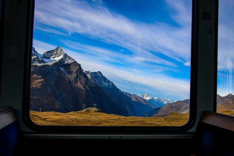 upptäck att Schweiz med det berömda traditionella schweiziska järnväg drevet irrar till och med majestätiskt alpint landskap arkivbilder