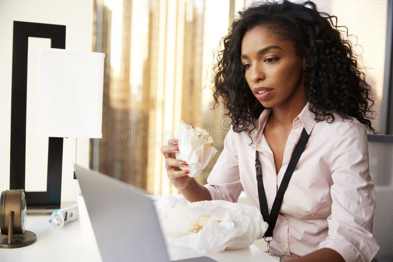 Upptagen affärskvinna With Laptop Sitting på skrivbordet som har smörgåsen för arbetelunch royaltyfria foton