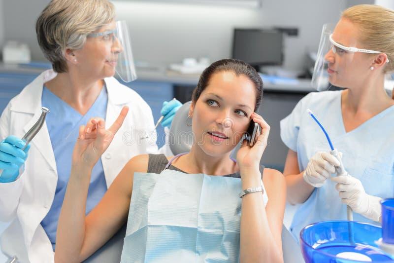 Upptagen affärskvinna på tand- kirurgi på telefonen royaltyfria foton