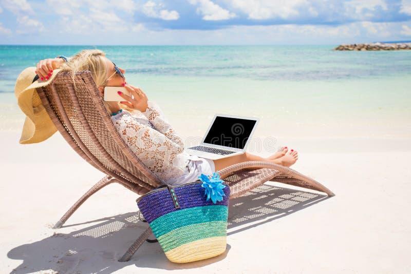 Upptagen affärskvinna som arbetar på stranden arkivfoto