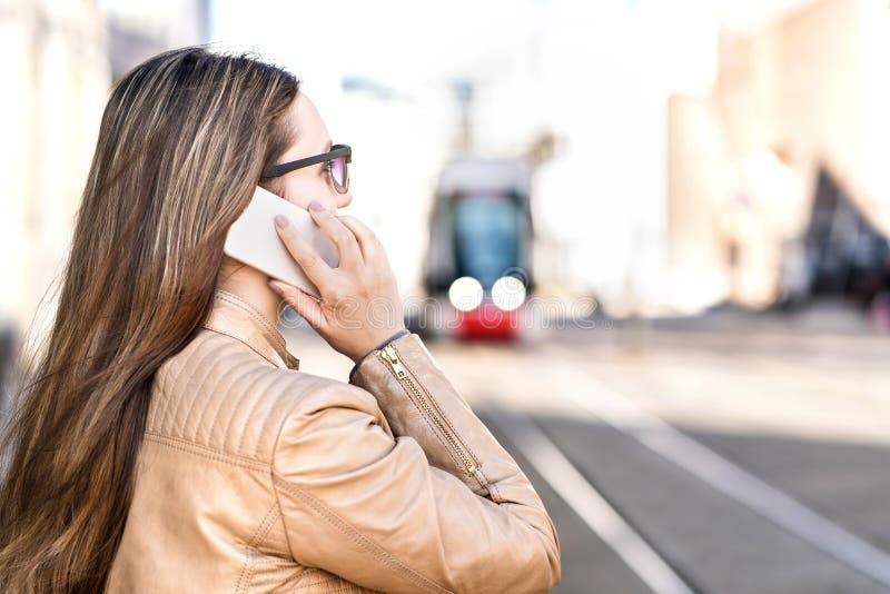 Upptagen affärskvinna som har en påringning, medan vänta på spårvagnen royaltyfri foto