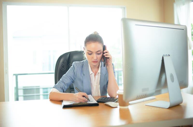 Upptagen affärskvinna som talar på telefonen, tar anmärkningar och arbetar nolla arkivfoto