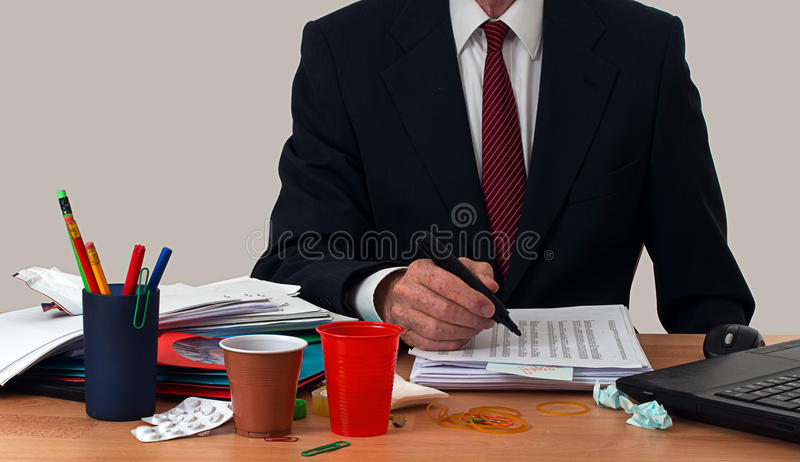 Upptagen affärsman eller kontorsarbetare, på det slarviga skrivbordet royaltyfria bilder