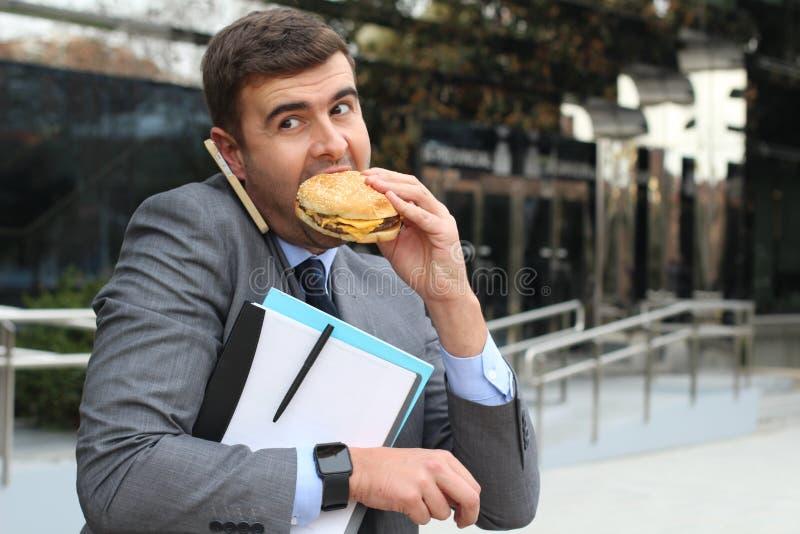 Upptagen affärsman som samtidigt går, kallar och har lunch arkivfoto