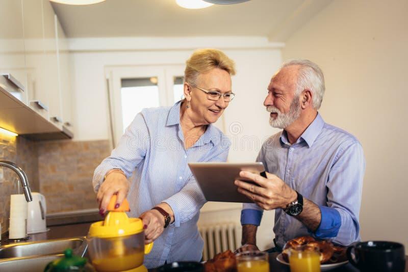Upptagen blick för par på den digitala minnestavlan, medan ha hemmastatt kök för läcker frukost royaltyfri bild