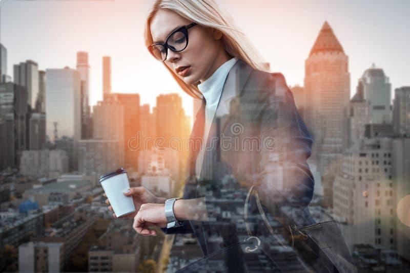 upptagen dag Härlig innehavkopp kaffe för ung kvinna och se hennes klocka, medan stå mot av modernt kontor fotografering för bildbyråer