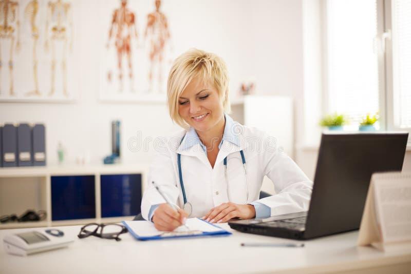 Upptagen doktor på hennes kontor royaltyfri bild
