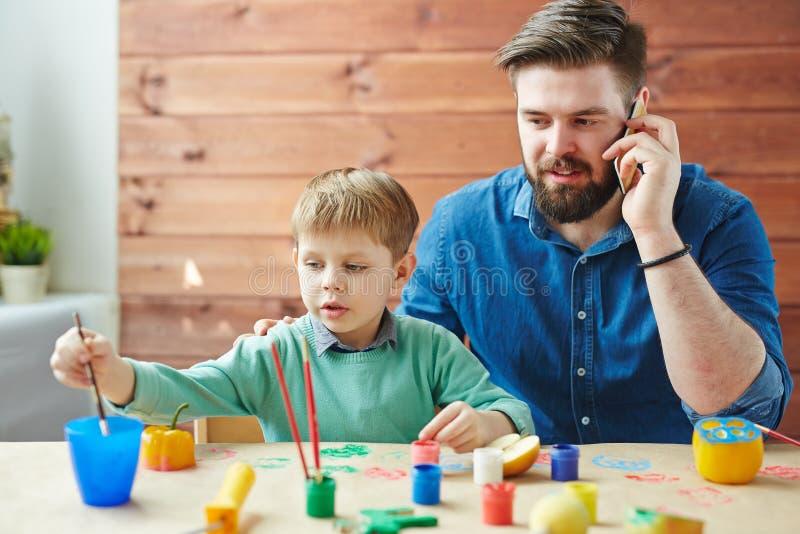 Upptagen fader som spenderar tid med hans son royaltyfria foton