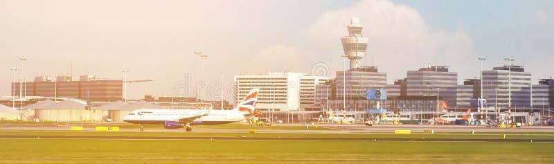 Upptagen flygplatssikt med flygplan och servicemedel på solnedgången flygplats med flygplan på portar och att ta av och solinstäl arkivfoton