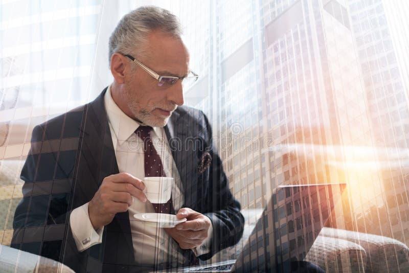 Upptagen funktionsduglig gentleman som dricker kaffe på bärbara datorn royaltyfri fotografi