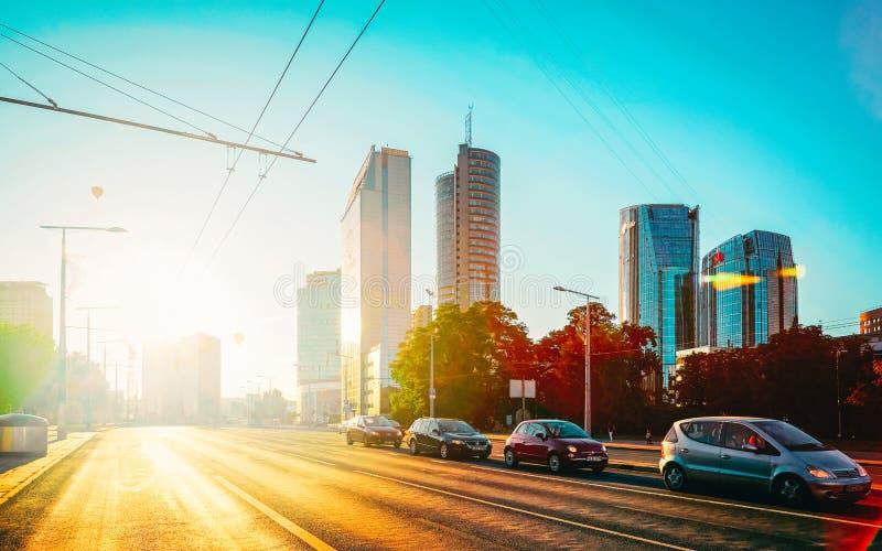 Upptagen gata med kommersiell arkitektur av moderna stål- och exponeringsglasskyskrapor på solnedgången royaltyfri fotografi