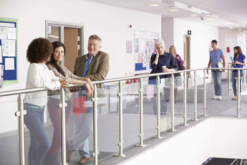 Upptagen högskolakorridor med moget studentsamtal fotografering för bildbyråer