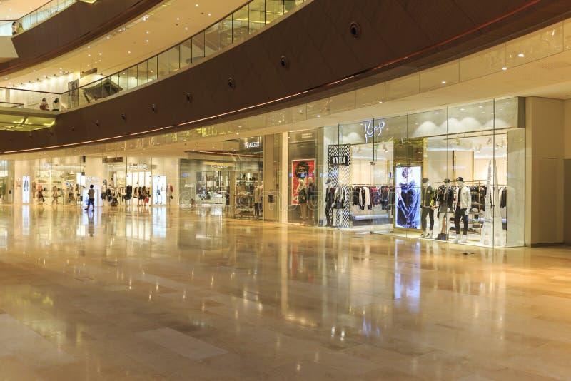 Upptagen interriorshoppinggalleria i Guangzhou Kina; modern köpcentrumkorridor; lagra mitten; shoppa fönstret arkivfoton