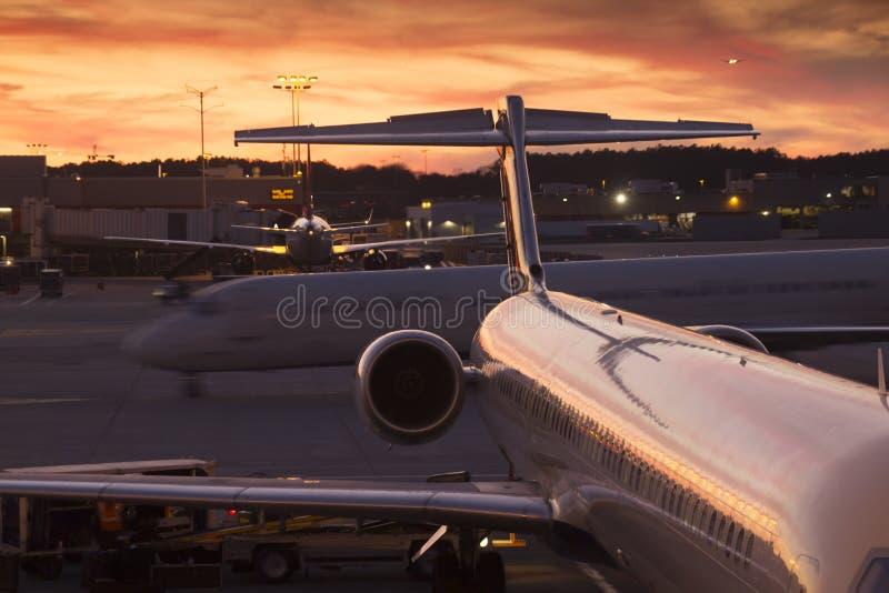 Upptagen kommersiell Aiport terminal på solnedgången royaltyfri foto