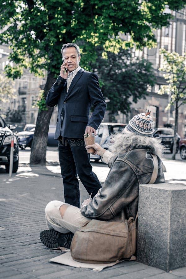 Upptagen kort-haired man som har påringning och kastar pengar arkivbild