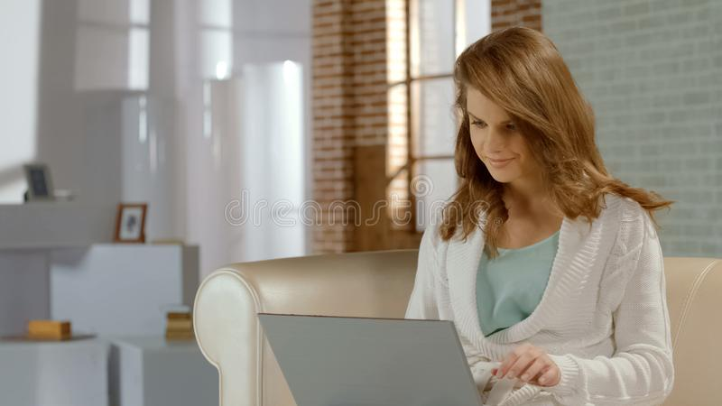 Upptagen lycklig tillfällig flicka och att arbeta på projekt genom att använda bärbara datorn hemma, frilans- royaltyfria foton