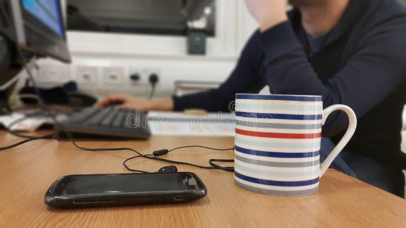 Upptagen man som arbetar sent sammanträde på skrivbordet royaltyfri bild