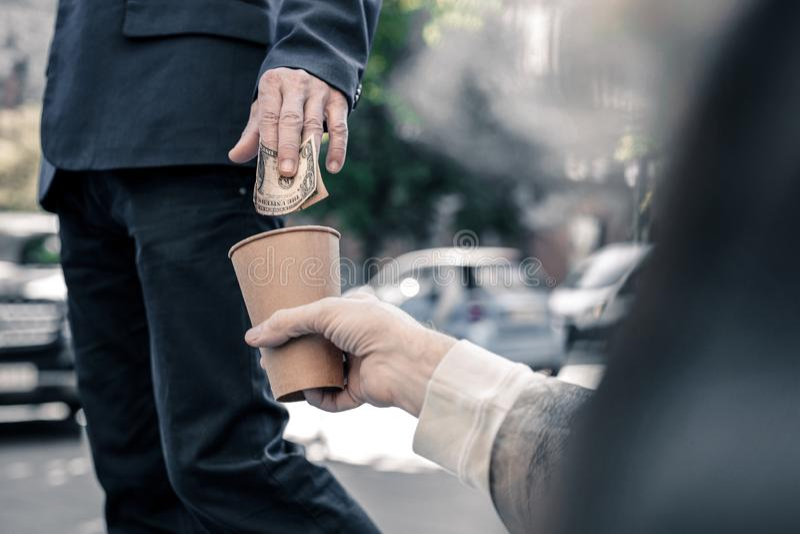 Upptagen oförsiktig affärsman som kastar pengar in i behållaren arkivbild