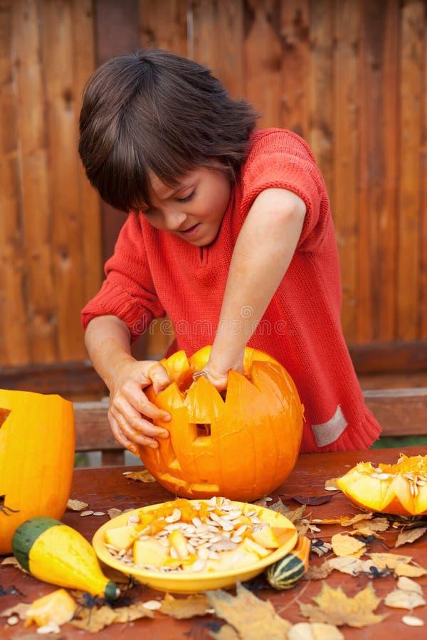 Upptagen pojke snida en pumpastålar-nolla-lykta för allhelgonaafton arkivbild
