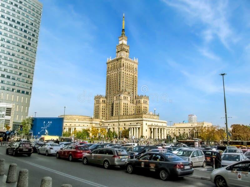 Upptagen stadsgata med m?nga bilar i bakgrunden av slotten av kultur och vetenskap i central Warszawa arkivfoton