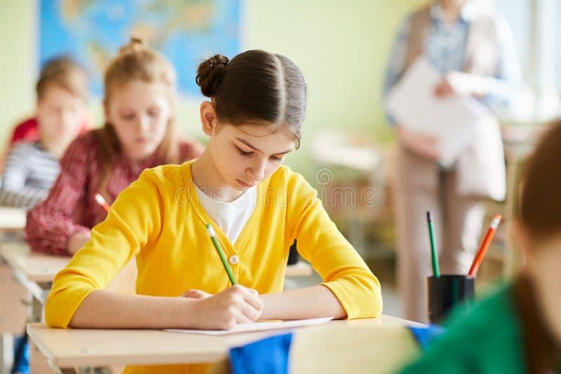 Upptagen studentflicka som koncentreras på frågesport arkivbild