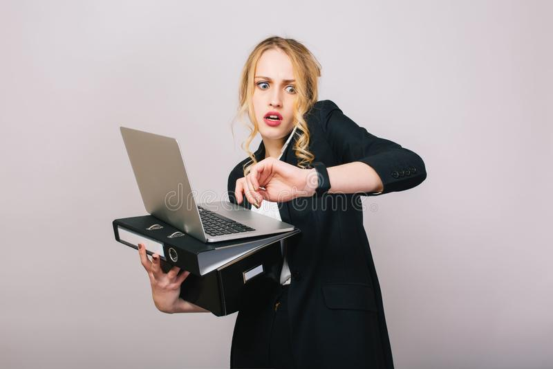 Upptagen tid för arbetskontor av den blonda unga kvinnan i formell kläder med bärbara datorn, mapp som talar på telefonen på vit  royaltyfri bild