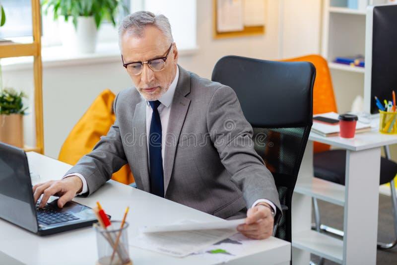 Upptagen trött grå färg-haired man i klara exponeringsglas som läser legitimationshandlingar och kontrollerar bärbara datorn arkivbild