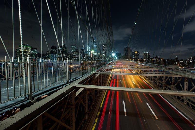 Upptagen trafik för skymning över den Brooklyn bron med Lower Manhattan Skyl fotografering för bildbyråer
