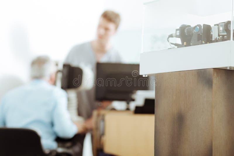 Upptagen undersökande patient för ögonläkarekänsla i ljust rum royaltyfri foto