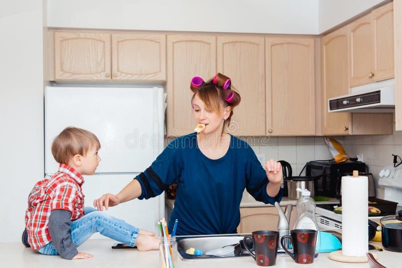 Upptagen vit Caucasian moderhemmafru för ung kvinna med papiljotter i hennes hårmatlagning som förbereder matställemål i kök royaltyfri foto