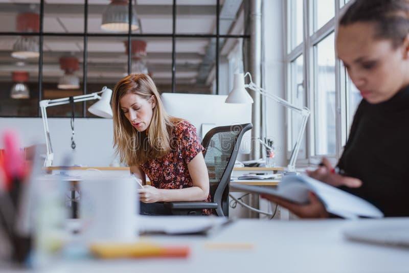 Upptaget arbete för ung kvinna på hennes skrivbord royaltyfria bilder