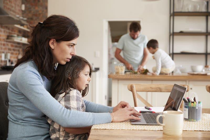 Upptaget familjhem med moderarbete som fadern Prepares Meal royaltyfria bilder