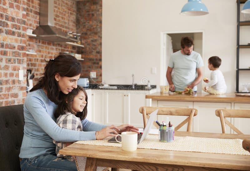Upptaget familjhem med moderarbete som fadern Prepares Meal royaltyfria foton