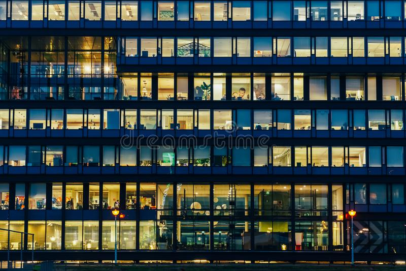 Upptagna kontorsbyggnader under natt i den Amsterdam staden arkivbild