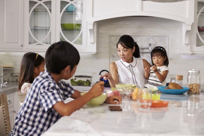 Upptagna moderuppläggningbarn på frukosten i kök royaltyfri bild