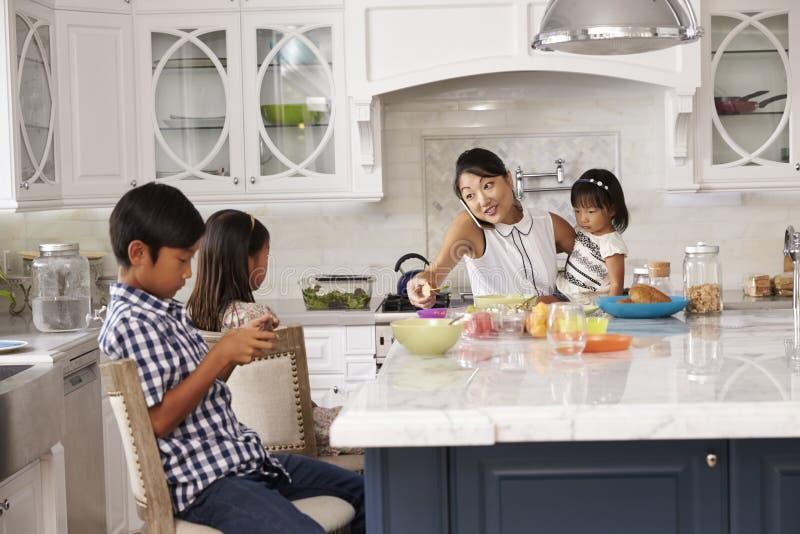 Upptagna moderuppläggningbarn på frukosten i kök arkivbilder