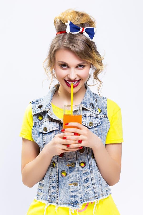 Upptakt och lycklig Caucasian blond flicka med orange fruktsaft och sugrör arkivfoton