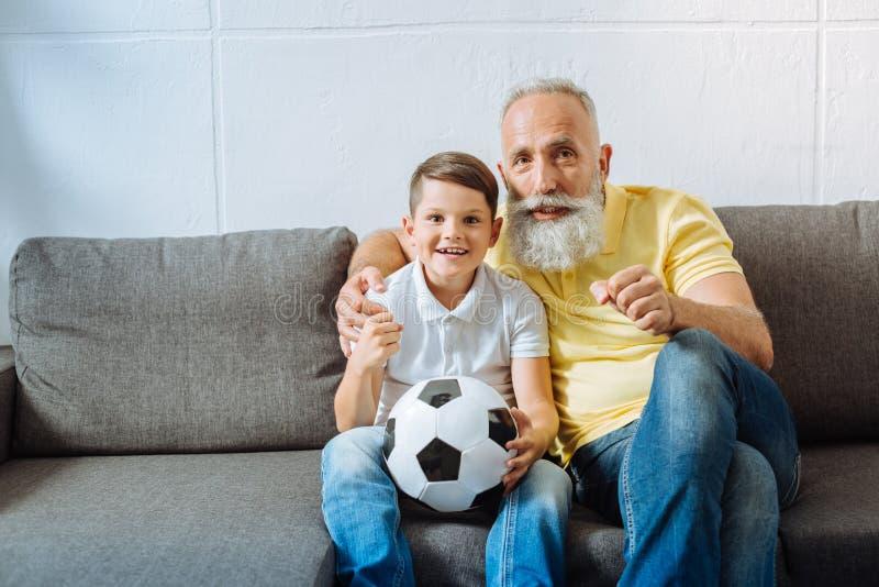 Upptaktfarfar och sonson som stöttar deras favorit- fotbollslag fotografering för bildbyråer