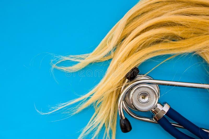 Upptar blondinen och stetoskopet för färg för mänskligt hår för krullning på blå bakgrund halva av fotoet, i andra halvan - tomt  royaltyfri foto