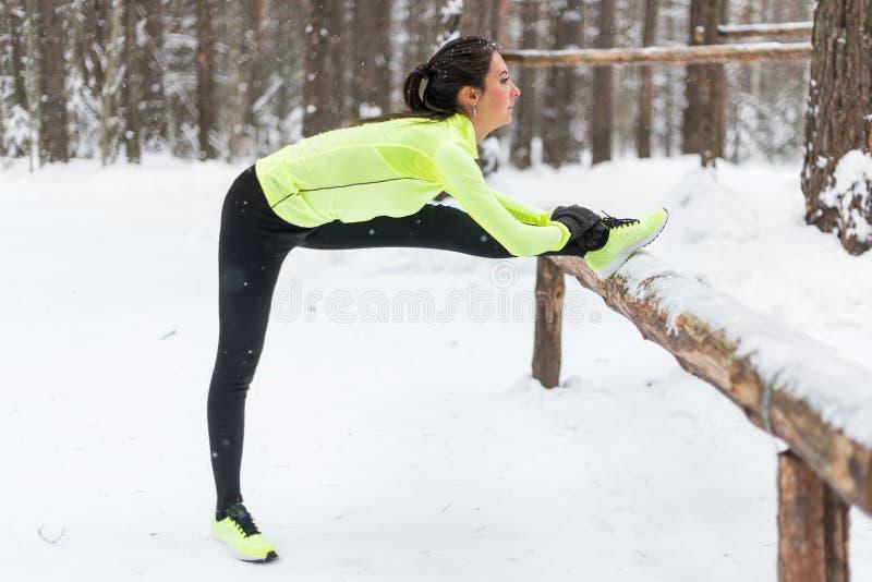 Uppvärmning för flicka för idrottsman nen för modell för vinterutbildningskondition som sträcker hennes knäsena, ben och baksida arkivfoto