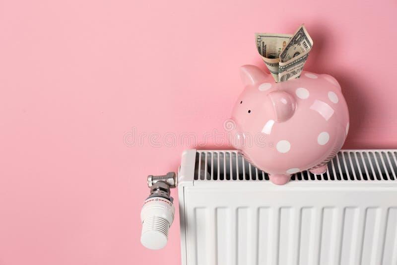 Uppvärmningelement och spargris med pengar på färgbakgrund royaltyfria foton