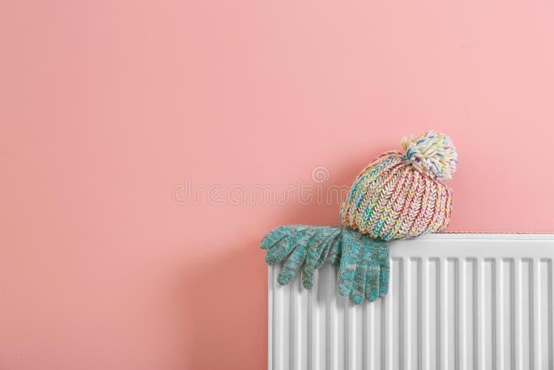 Uppvärmningelementet med luvan och handskar nära färgar väggen royaltyfria foton