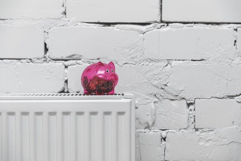 uppvärmningkostnader - spargris på elementet framme av den vita väggen arkivbild