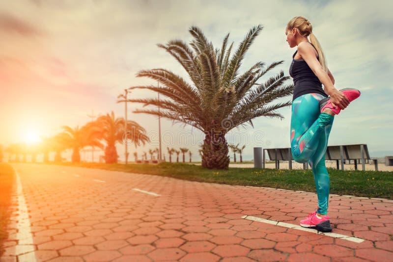 Uppvärmningsben för ung kvinna, innan att jogga för start arkivbild