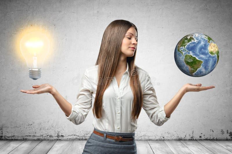 Uprawa wizerunek m?ody pi?kny bizneswoman, r?ki przy stronami, palmy stawia czo?o w g?r?, levitating lightbulb i ma?a ziemia, zdjęcia stock
