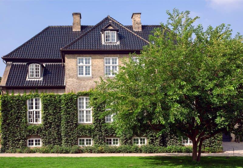 Uprawia ogródek wokoło pięknych ściana z cegieł dziejowy dom w Kopenhaga, Dani tradycyjna architektury obraz stock